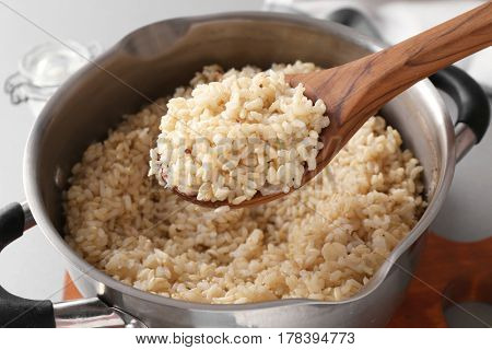 Spoon with prepared brown rice over saucepan