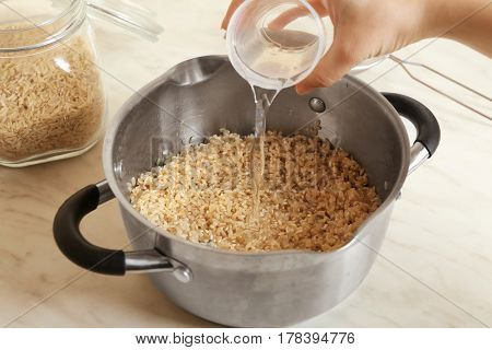 Female hand pouring water into pan with brown rice, closeup