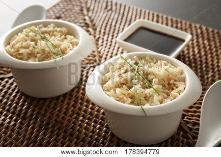 Two bowls with brown rice on wicker mat