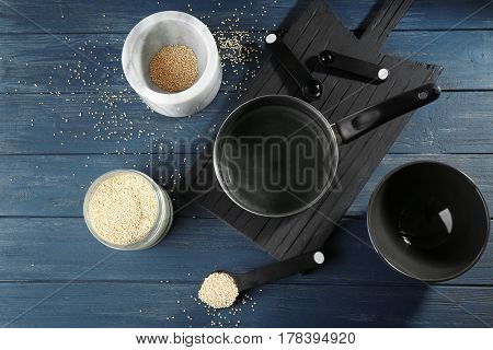 Kitchen utensils and quinoa seeds on wooden table