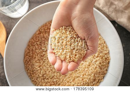 Woman holding heap of brown rice over white bowl