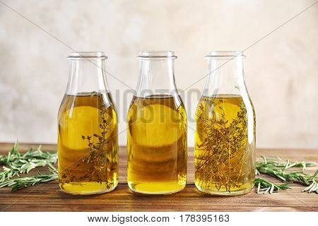 Bottles with herbs and oil on table