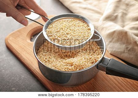 Woman holding sieve with rice over pan on cutting board