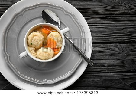 Decorative plate with soup pot of chicken and dumplings on black wooden background