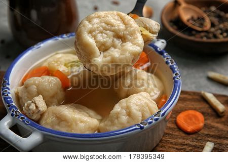 Spoon with delicious chicken and dumplings above pot on kitchen table