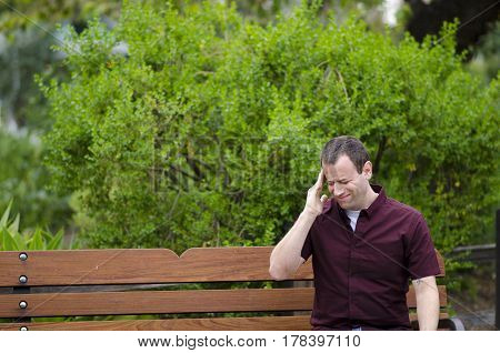 Stressed out man with a headache with his hand on his temple.