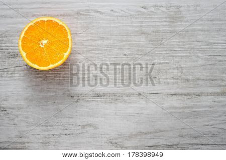 Single round slice of fresh orange on white wood background, Top view, lot of copyspace