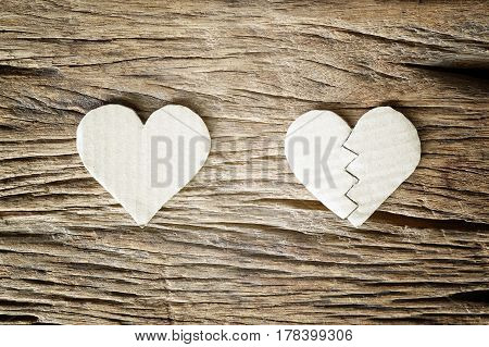 heart and broken heart paper cut on wooden background - love concept