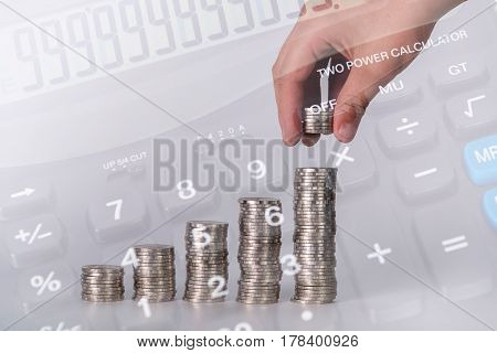 Double Exposure Of Hand Put Money Coins To Stack Of Coins And Blurred Calculator And Money Backgroun