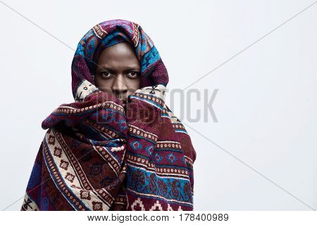 Human face expressions and emotions. Close up portrait of unhappy scared anxious worried craving for something African American male looking at the camera covered with ethnic blanket. Isolated on white background.