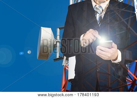 Double Exposure Of Businessman Using Smart Phone On Blue Sky And Telecommunication Tower Background.