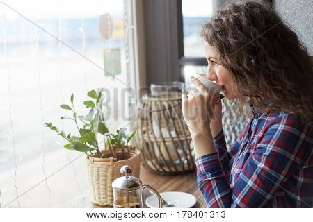 Close up portrait of attractive Caucasian lady taking a sip of tea in modern coffee shop looking at the window waiting for friends meeting sitting near copy space area for your advertising messages or content