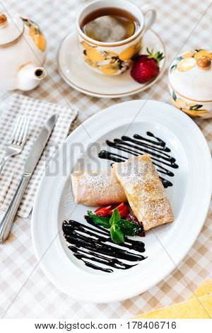 Pancakes, beautifuly decorated with chocolate, fresh strawberry, mint and powdered sugar