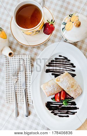 Pancakes, beautifuly decorated with chocolate, fresh strawberry, mint and powdered sugar, with cup of tee
