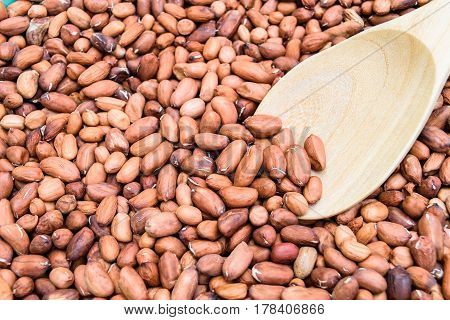 Raw peanuts or arachis in wooden spoon