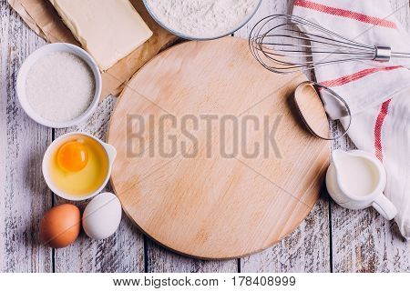 Ingredients for baking Easter cake - eggs flour milk butter sugar) and utensils on white wooden background. Baking dark background with blank cook book or copy space top view