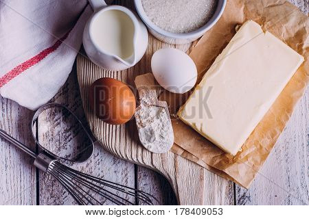 Ingredients for baking Easter cake - eggs flour milk butter sugar) and utensils on white wooden background. Baking dark background with copy space top view