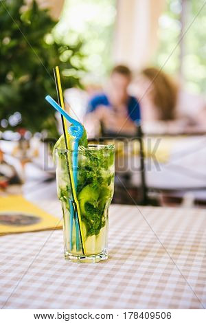 Mojito with blue straws, lemon wedge and mint in high glass