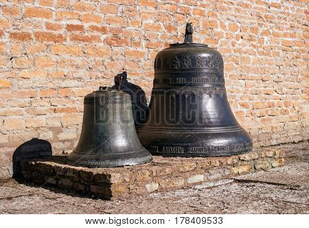 Narva Estonia - March 16 2017: Traditional old church bells in Narva citadel. The surface is decorated with inscriptions and decorations.