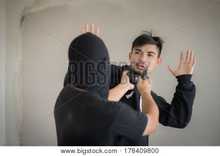 Men thief threatening handsome young man with gun