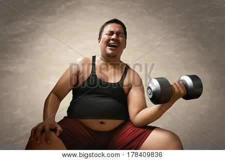 Fat man lifting weights and feel tired