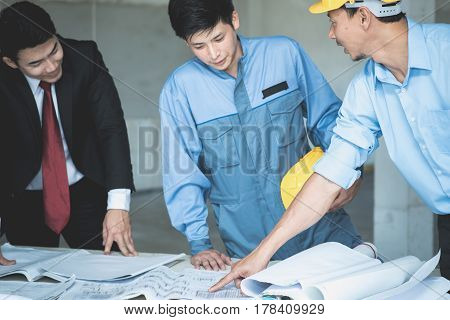 Group of engineers and architects discuss at a construction site with blueprint Architecture and Engineering concept