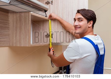 Young man assembling kitchen furniture
