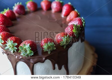 Delicious cake with fresh strawberry and dark chocolate sauce, close-up