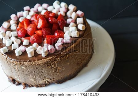 Delicious cake with fresh strawberries and dark chocolate sauce and plate with marshmallows