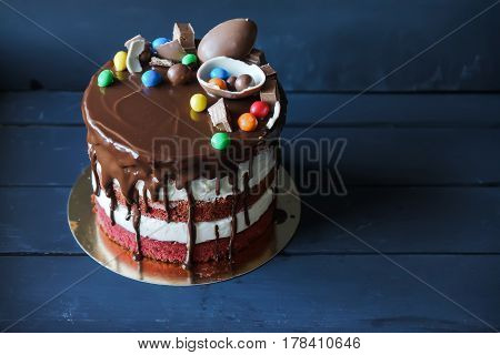 Delicious chocolate cake with dark chocolate sauce and with chocolate candies