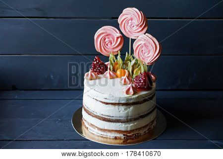 Beautiful small cake with candies, fruit and meringue docoration on dark blue background