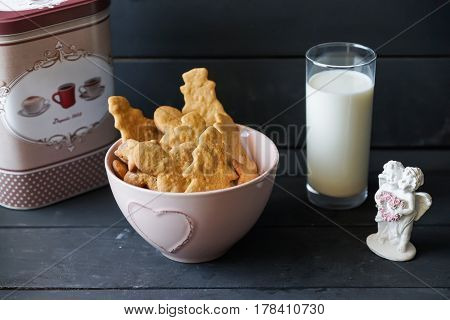 Christmas cookies in pink plate with fresh milk and small sculpture of angels