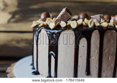 Delicious cake with peanut and dark chocolate sauce and pieces of Snickers candy