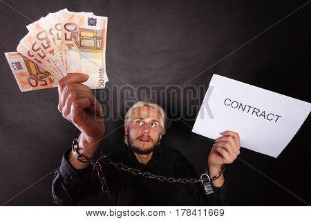 Stress at work no freedom pursuit of money concept. Man with chained hands choosing between money and contract studio shot on dark grunge background