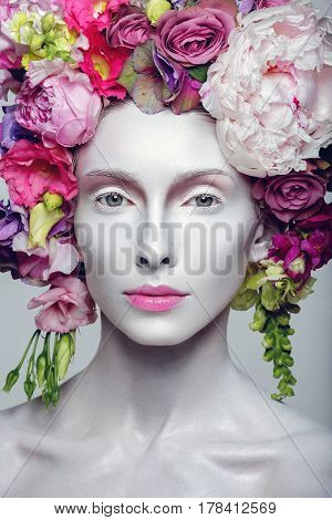 Beautiful young pale white woman with different flowers on head. Flower queen. Beauty shot.