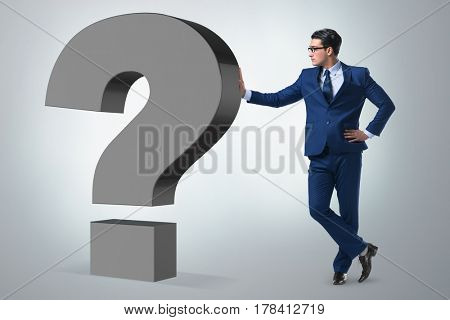 Businessman next to the giant question mark