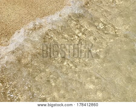 Clear ocean water washing over sand on a tropical island. Great background image for summer themes.