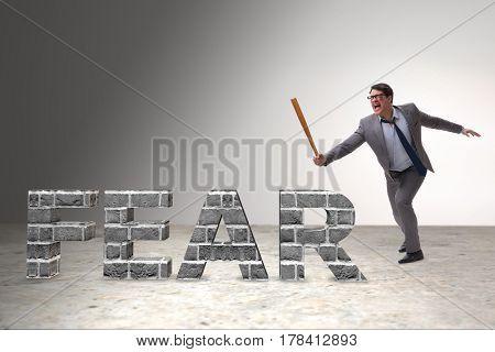 Angry man with baseball bat hitting fear word