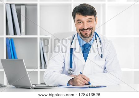 Portrait of smiling mature doctor in a clinical office