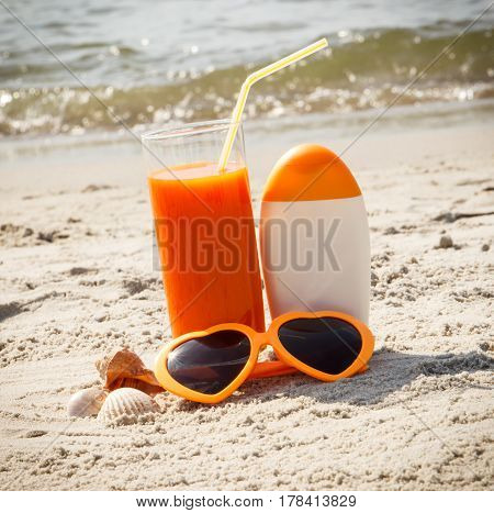 Carrot Juice, Sunglasses And Sun Lotion At Beach, Concept Of Vitamin A And Beautiful, Lasting Tan