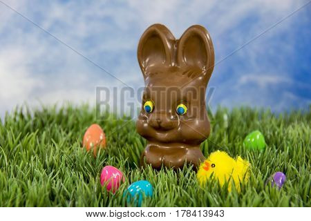 chocolate Easter bunny with yellow chick and colorful eggs in grass