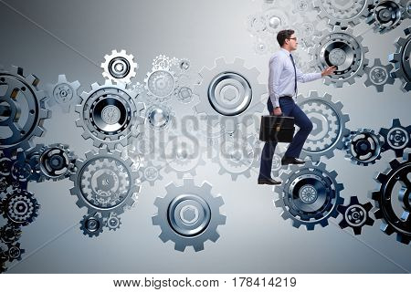 Businessman in teamwork concept with cog wheels