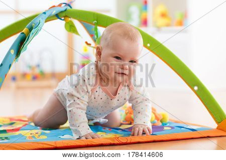 Unhappy seven months baby girl crawling on colorful playmat in nursery