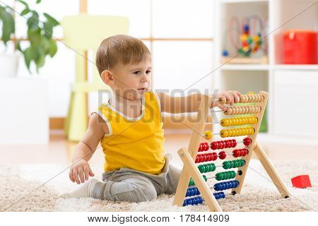 child boy playing with abacus in nursery
