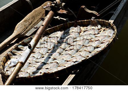 Dried fish in threshing basket on boat.
