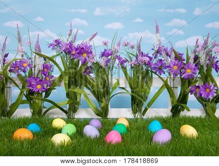 Colorful Easter Eggs scattered in tall grass in front of a picket fence with purple flowers. Blue background sky with clouds.