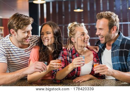 Friends laughing inside a bar with shots in hand