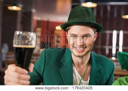 Man with a hat toasting a beer in a bar