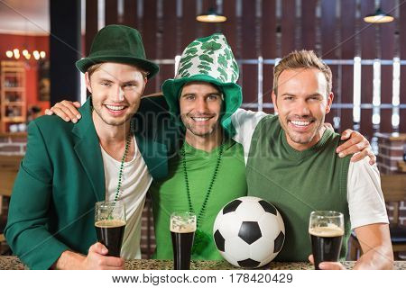 Friends with paddys day clothing smiling at camera