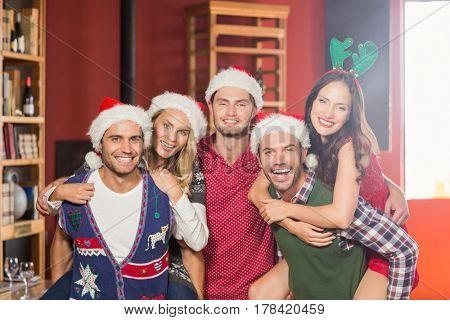 Men wearing Christmas wearing giving women piggyback rides in a bar